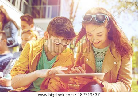 education, high school and people concept - group of happy teenage students with tablet pc computers at campus yard