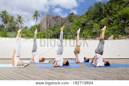 yoga, fitness, sport, and healthy lifestyle concept - group of people making supported shoulderstand pose on mat outdoors over exotic tropical beach background