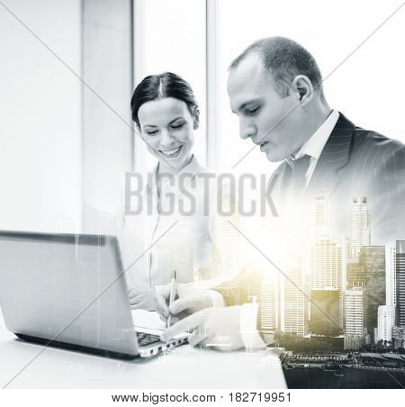 business, technology and people concept - smiling team with laptop computer working at office over city buildings and double exposure effect