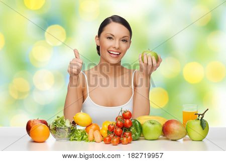 diet, healthy eating, food and people concept - beautiful woman with fruits and vegetables showing thumbs up over green summer lights background