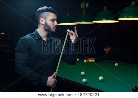 Attractive young caucasian or middle eastern man preparing cue for playing billiard. Green pool table background