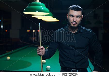 Male caucasian or middle eastern adult wearing black casual cloth standing with snooker cue. Young man playing billiard game at pub.