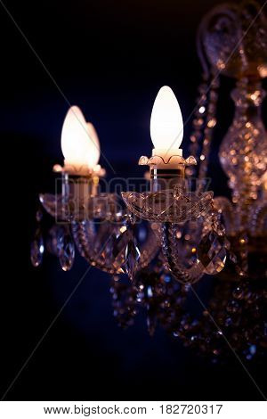 A burning light bulb on a crystal chandelier on a dark background