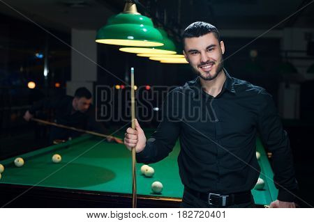 Young smiling man wearing black casual cloth standing with snooker cue. Two male friends playing billiard in club.