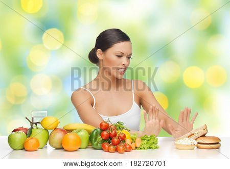 diet, healthy eating, food and people - woman with fruits and vegetables rejecting hamburger and sandwich on table over green summer lights background