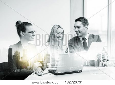 teamwork, corporate, technology and people concept - smiling business team with laptop computer and papers having discussion at office over city buildings and double exposure effect