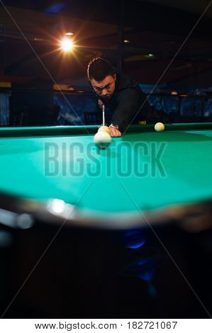 Young man aiming billiard ball. Male adult playing snooker alone.