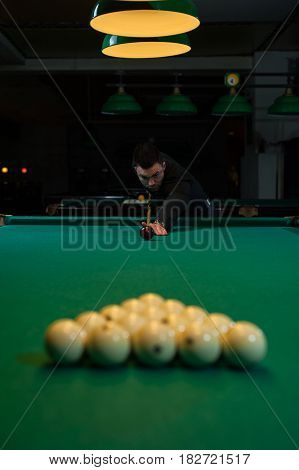 Concentrated man aiming the billiard ball. Snooker game background. Shallow depth of field.