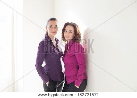 two girls in purple are the white walls