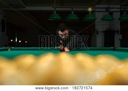 Playing billiard background - young concentrated man aiming to take snooker shot.