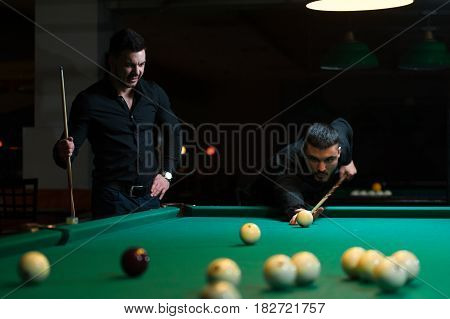 Two male friends wearing black casual cloth playing billiard game in dark club. Young man aiming to take a snooker shot.
