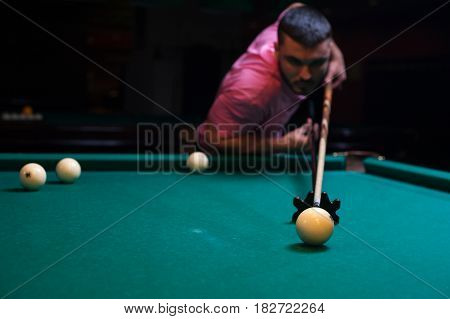 Young concentrated man aiming to take the snooker shot. Male adult playing billiard game. Shallow depth of field.