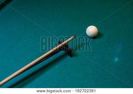 Playing billiard background - cue with white snooker ball on green table.