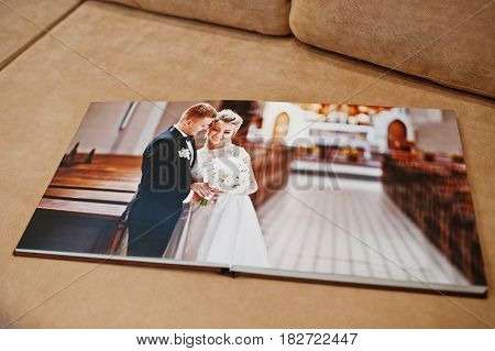 Two Open Pages Of Wedding Book On Sofa.