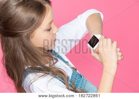 High Angle View Of Cute Little Girl Using Smartwatch On Pink