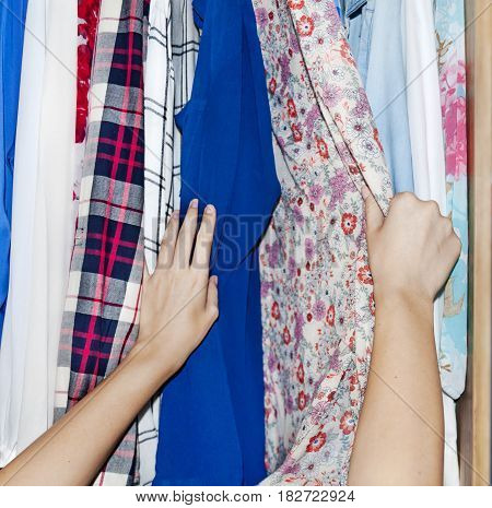 Woman pointing at clothes in closet  close