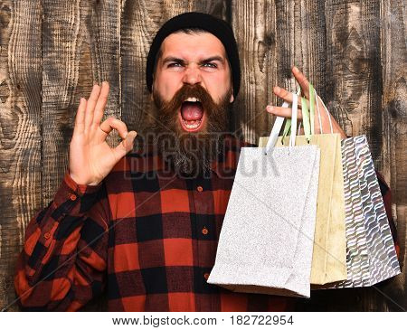 Bearded man long beard. Brutal caucasian shouting hipster with moustache holding shopping packages in red black checkered shirt on brown wooden vintage studio background