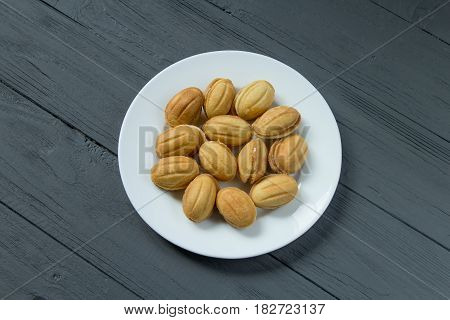 Homemade cookies with condenced milk on a white plate, top view