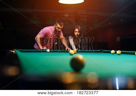 Young romantic couple having fun playing billiard game in dark club. Young brunette girl aiming to take a snooker shot, while man standing next to her and looking at table.