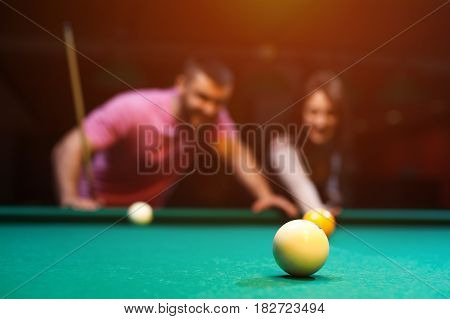 Young romantic couple having fun playing billiard game in dark club. Young brunette girl aiming to take a snooker shot, while man standing next to her and looking at table. Defocused background.