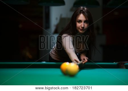 Attractive brunette girl playing billiard game. Young caucasian woman with cue on the background of green snooker table.