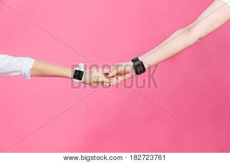 Close-up Partial View Of Mother And Daughter With Smartwatches Holding Hands On Pink