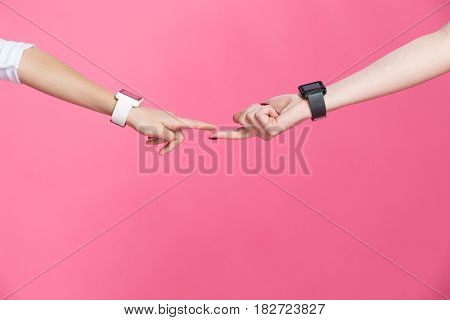 Close-up Partial View Of Mother And Daughter With Smartwatches Touching Fingers