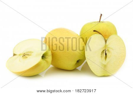 fresh yellow apples and a cut one on a white background