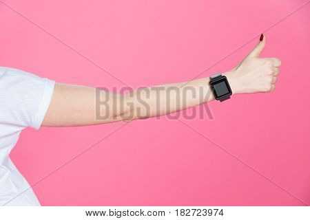 Close-up partial view of woman with smartwatch showing thumb up on pink