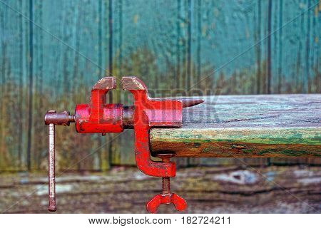 Red old metal grip screwed onto a wooden board