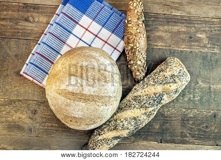 Baking dietary various bread isolated on wooden table on dishcloth