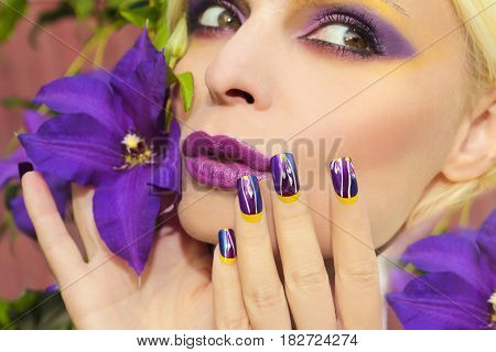 Lilac summer makeup and manicure with a design on the nails on the woman with the clematis closeup.Nail art.