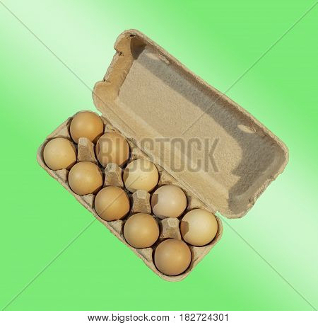 Carton package, Ten brown eggs in a carton package isolated on green and white background