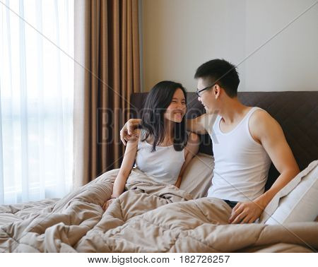 Asian Couple Looking Each Other On Bed In Luxury Bedroom