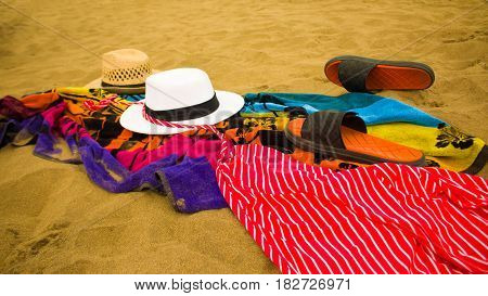Top view of sandy beach with summer accessories. Background with copy space and visible sand texture.