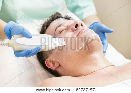 Man in the mask cosmetic procedure in spa salon