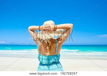Romantic woman in dress and hat is enjoying serene ocean nature during travel holidays vacation outdoors. Happiness bliss freedom concept.