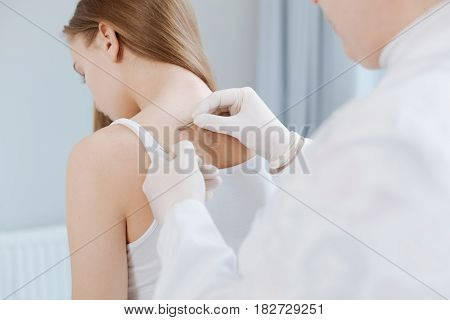 Daily routine in the medical laboratory. Concerned female motionless patient sitting in the clinic and expressing concentration while doctor using tools for getting skin analysis