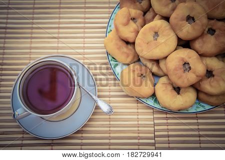 Hot tea in a cup with a saucer and tatar meat pies peremyach