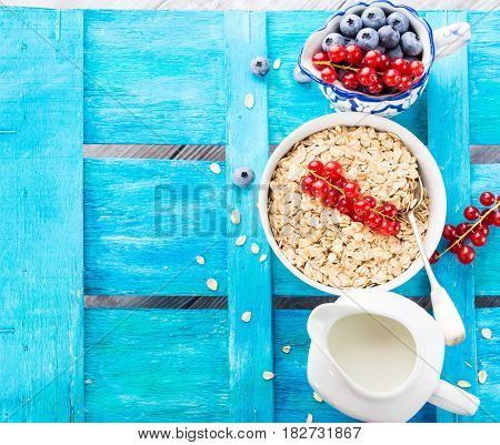 Rolled Oats And Berries On Blue Textured Background