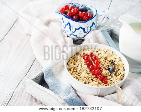 Raw Rolled Oats With Fresh Berries On Wooden Table