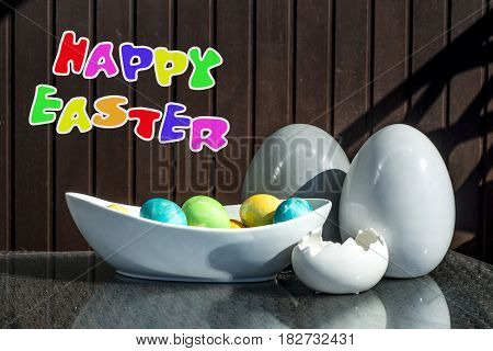 Set of colorful shiny Easter eggs and grey and white colored ceramic with text happy easter