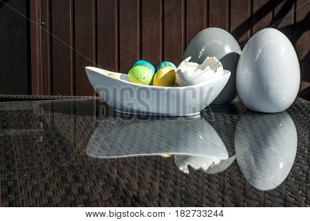 Set of colorful shiny Easter eggs and grey and white colored ceramic and reflection on table