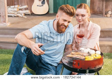 Man And Woman Roasting Meat And Vegetables On Barbecue Grill, Woman Holding Wineglass