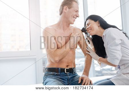 Enjoying skincare appointment . Delighted optimistic professional dermatologist working in the hospital and listening to the patient complaint while examining man torso and using special instrument