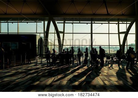 Crowd of passenger with luggage waiting in departure area in airport terminal.