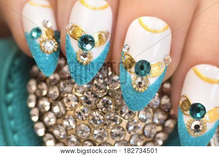 Luxurious glamorous sandy blue French manicure with rhinestonesboulongne and gold plated women's nails closeup.