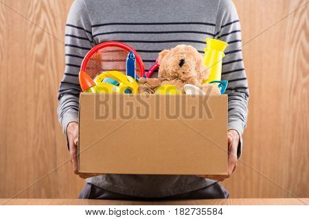 Male Volunteer Holding Donation Box With Old Toys.