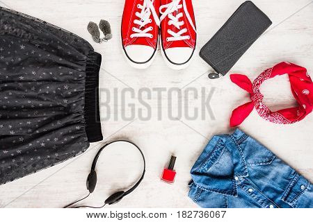 Top view of yong woman clothes and accessories. Tulle skirt denim shirt wallet head phones earrings nail polish sneakers and kerchief. Urban style concept.