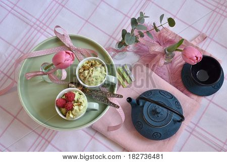Teapot and teacup, Marrakech design. Top view. Pistage icecream, raspberries, pink tulips, eucalyptus, pastels. Pink and green.